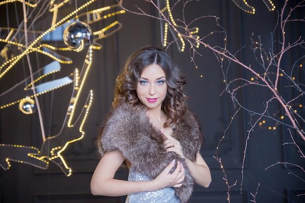 Sexy mode vrouw draagt in winter bontjas op vervagen feestelijke achtergrond. jonge vrouw in bontjas met rode lippen staat op de jaarmarkt op de glitter garland achtergrond. rond de lichten en