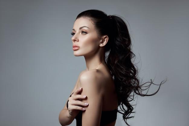Sexy mode vrouw met lang haar, sterke krullend haar van een brunette meisje in lingerie.