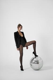 Sexy mode vrouw op witte kamer in de buurt van discobal, mooi slank lichaam van vrouw