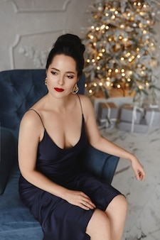 Sexy model meisje met modieus kapsel in de donkerblauwe jurk poseren met feestelijke verlichting op de achtergrond in ingericht voor kerstmis interieur.