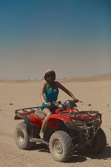 Sexy model meisje met perfect lichaam en bruin, in zonnebril en helm, zittend op atv en poseren in de woestijn. vrouwelijke rijder die het stuur houdt en op off-road in de woestijn poseren