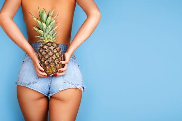 Sexy modelmeisje met ananas op haar rug