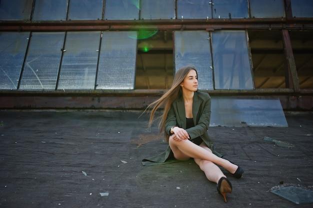 Sexy modelmeisje met lange benen bij zwart het lichaamszwempak van de lingerieuitrusting combidress en jasje gesteld bij het dak van verlaten industriële plaats met vensters.