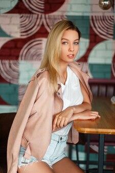Sexy mooi amerikaans meisjesmodel in een roze jasje en denimborrels die in een koffie zitten