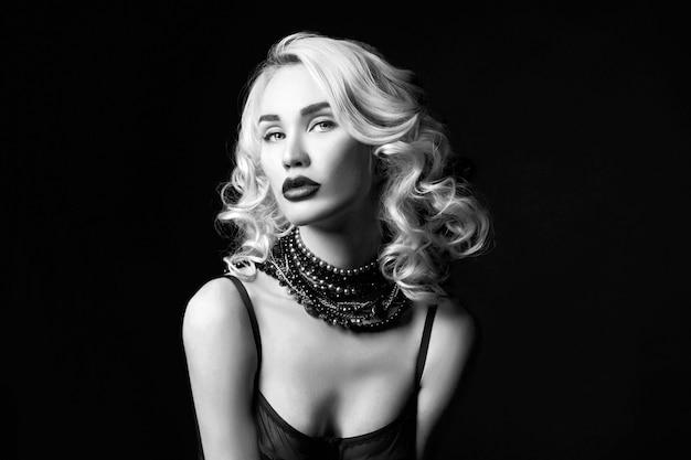 Sexy mooi blondemeisje met lang haar. perfect vrouwenportret op zwarte muur. prachtig haar en mooie ogen. natuurlijke schoonheid, schone huid, gezichtsverzorging en haar. sterk en dik haar. sieraden