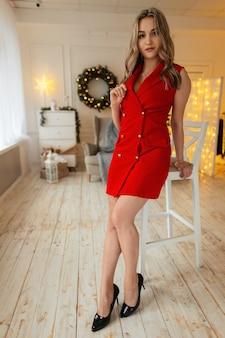Sexy mooi jong meisje in een modieus elegant rood pak staat in de buurt van een stoel tegen de achtergrond van kerstversieringen en gouden lichten