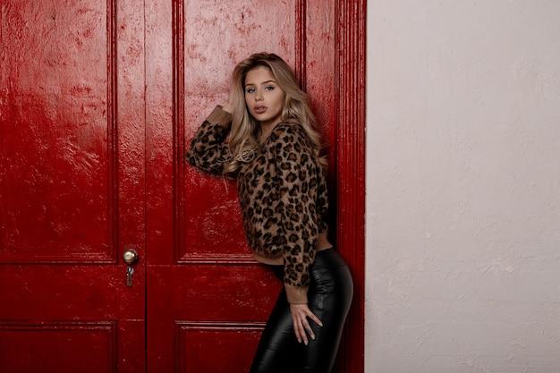 Sexy mooie jonge blonde vrouw met krullend haar in een stijlvolle luipaard trui in modieuze zwart lederen broek vormt binnenshuis bij de vintage houten rode deur