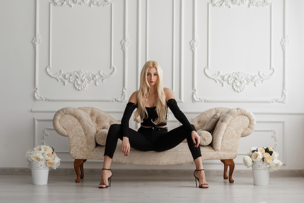 Sexy mooie jonge model vrouw in modieuze zwarte kleding met spijkerbroek zittend op een bank in een vintage kamer