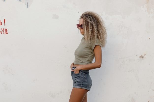 Sexy mooie jonge modelvrouw met krullend haar in een maniert-shirt en jeansborrels dichtbij een witte muur op het strand