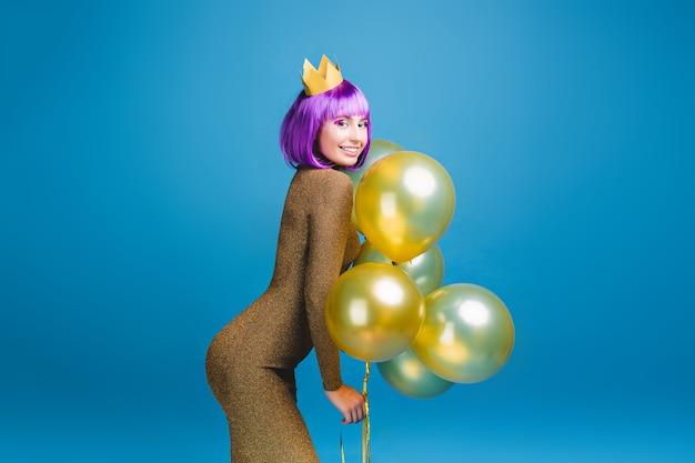 Sexy mooie jonge vrouw in modieuze luxe jurk met plezier met gouden ballonnen. knip paars haar, kroon, nieuwjaarsfeest vieren, verjaardag, glimlachen, geluk.
