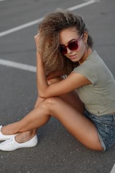 Sexy mooie jonge vrouw model met krullend haar in zonnebril met trendy denim kleding en stijlvolle schoenen zittend op het asfalt op de weg