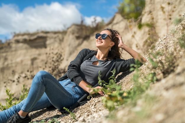 Sexy mooie jonge vrouw vormt casual kleding op zandgroeve. buitenshuis