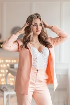 Sexy mooie vrouw in een modieus pak met een blazer en witte kanten lingerie met weelderige borsten staat in een schoonheidsstudio