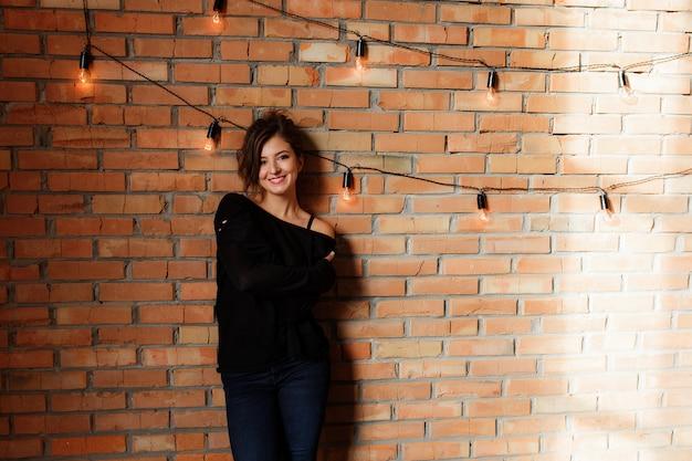 Sexy mooie vrouw in zwarte sweater en jeans die zich dichtbij een retro rode bakstenen muur bevinden