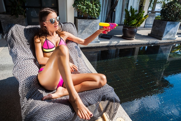 Sexy mooie vrouw met plezier met plastic waterpistolen spelen bij zwembad