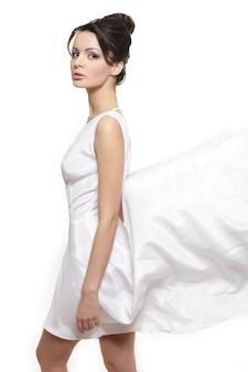 Sexy mooie vrouwendame die witte vliegende die kledingsbruid dragen op wit wordt geïsoleerd