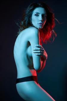 Sexy naakte vrouw in een riem in neonlicht. perfect figuur en borsten van een vrouw in ondergoed, mooi haar