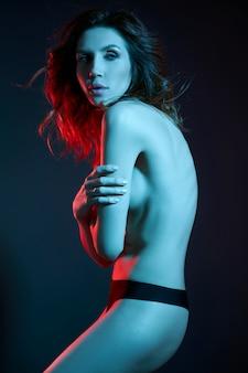 Sexy naakte vrouw in een riem in neonlicht