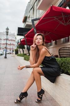 Sexy oman in elegante zwarte jurk en hakken met heldere blonde haren poseren in oude europese stad in de buurt van luxe restaurant.