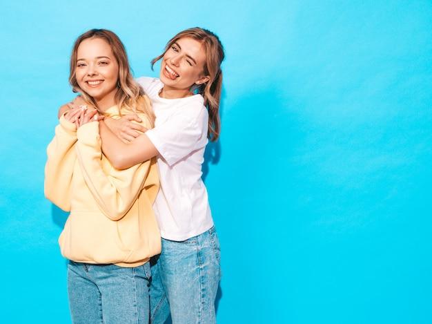 Sexy onbezorgde vrouwen die dichtbij blauwe muur stellen. positieve modellen met plezier en toont tong