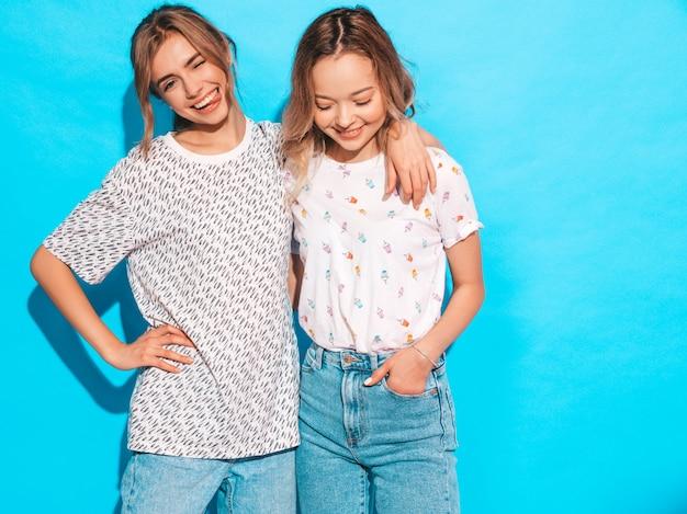 Sexy onbezorgde vrouwen die dichtbij blauwe muur stellen. positieve modellen met plezier. knipoogt en toont tong