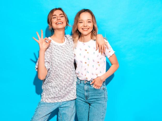 Sexy onbezorgde vrouwen die dichtbij blauwe muur stellen. positieve modellen plezier. toont ok teken