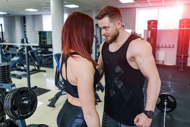 Sexy paar in sportkleding kijken elkaar in de sportschool. gespierde man en sportief meisje staan samen over de moderne sportschool.