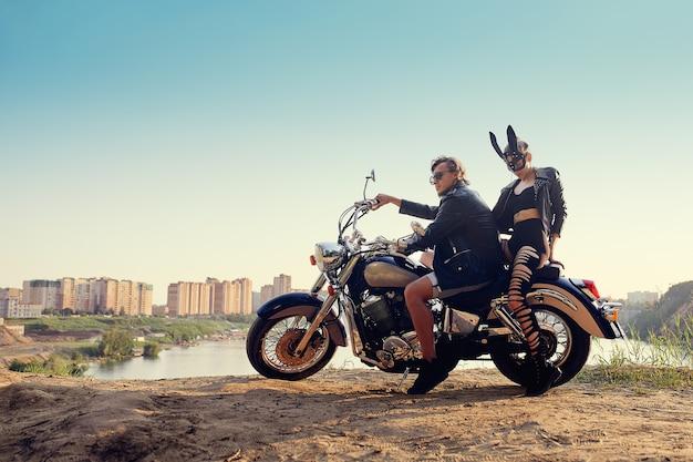 Sexy paar motorrijders op de vintage aangepaste motorfiets, meisje in een konijnenmasker
