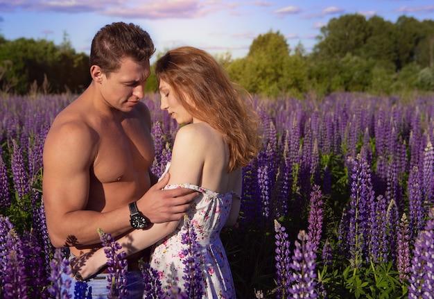 Sexy paar op een bloeiende veld op een zonnige dag.