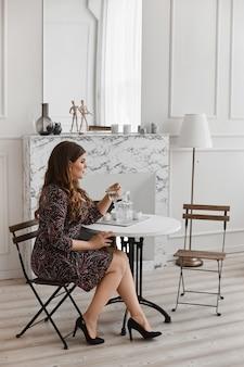 Sexy plus size model meisje in trendy jurk zitten aan de tafel en poseren in interieur. jonge dikke vrouw met lichte make-up en met stijlvolle kapsel in een modieuze outfit. xxl mode en beauty.