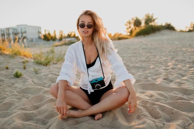 Sexy reizende vrouw ontspannen op het strand in warme zomeravond. zittend op zand. witte blouse en zonnebril dragen. retro camera vasthouden.