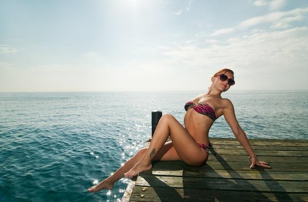 Sexy rode meisje dragen bikini bij de pier