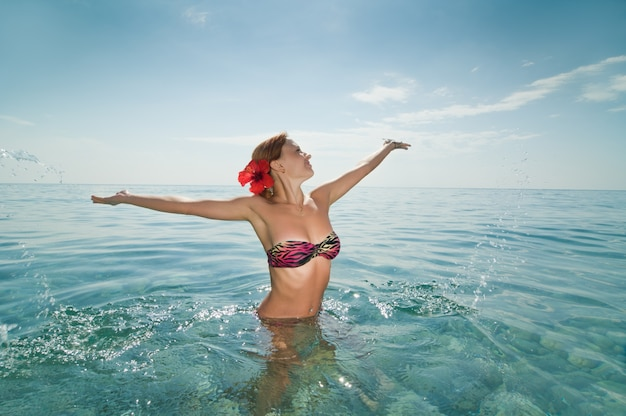 Sexy rode meisje dragen bikini genieten van water