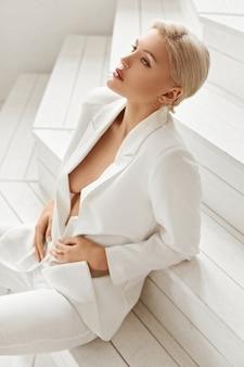 Sexy rondborstige jonge blonde modelvrouw met perfect lichaam in een pak