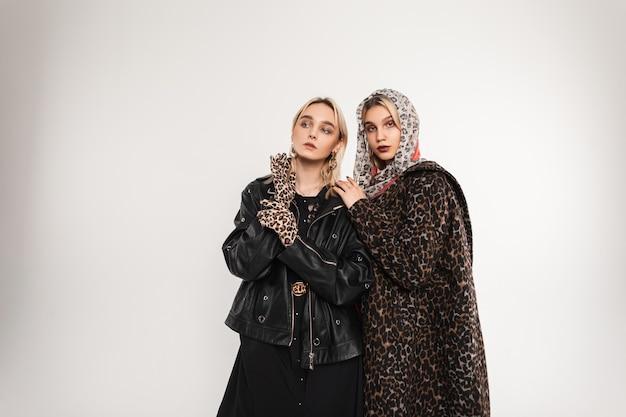 Sexy schattige blonde vrouw in stijlvolle oversized zwarte jeugdjas in elegante handschoenen en meisje mannequin met sjaal op hoofd in luxe luipaard jas poseren