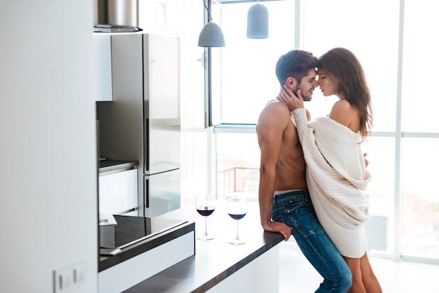 Sexy sensueel jong stel staat en knuffelt in de keuken