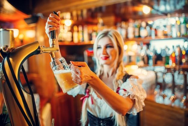 Sexy serveerster schenkt bier in een mok op het bureau
