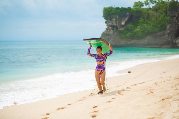 Sexy slank meisje met surfplank op tropisch zandstrand.