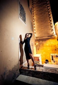 Sexy slanke vrouw in zwarte jurk poseren op straat 's nachts