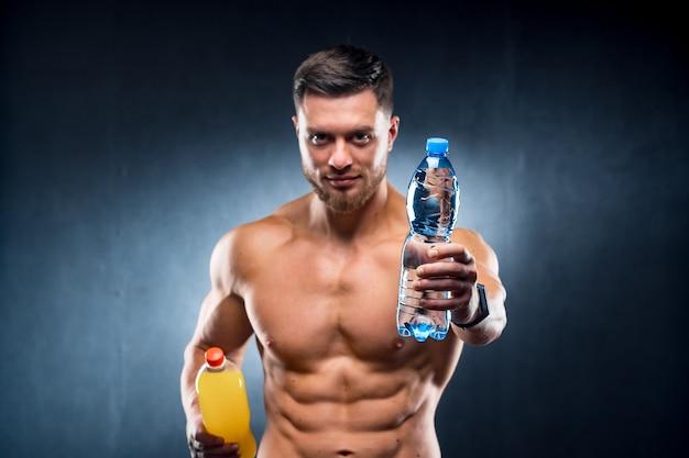 Sexy sportman met een fles water en frisdrank. kiezen tussen gezonde en schadelijke drank. portret. detailopname