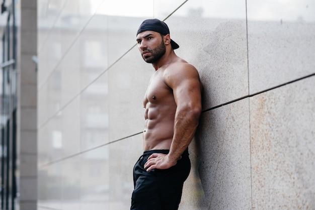 Sexy sportman staat topless bij de muur. fitness, bodybuilding.