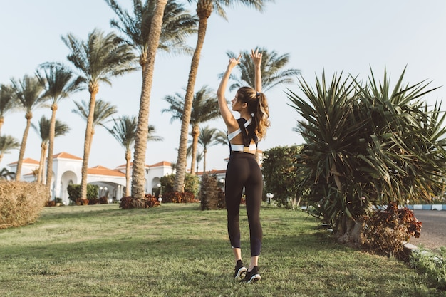 Sexy sportvrouw handen uitrekken op gras in tropische stad. zonnige ochtend, opgewekte stemming, motivatie, training, chillen met gesloten ogen, gezonde levensstijl, fitness, aantrekkelijk model