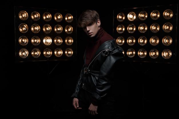 Sexy stijlvolle jongeman in een stijlvol kapsel in een modieuze leren jas in bourgondische golf vormt voor de camera in een donkere kamer op de achtergrond van heldere vintage elektrische lampen. aardige man