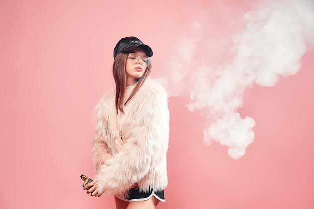 Sexy trendy rap vrouw in roze bontjas en pet elektronische sigaret roken op roze