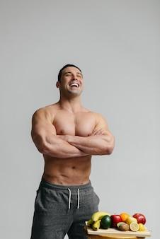 Sexy veganistische man met een naakte torso poseren in de studio naast fruit. eetpatroon. gezond dieet