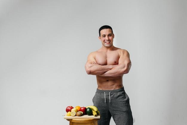 Sexy veganistische man met een naakte torso poseren in de studio naast fruit. eetpatroon. gezond dieet.