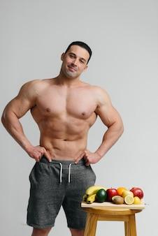 Sexy veganistische man met een naakte torso poseren naast fruit. eetpatroon. gezond dieet