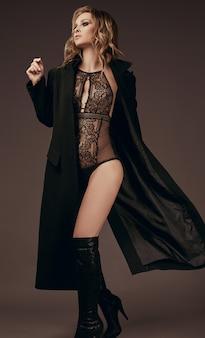 Sexy verleidelijk blond meisje in ondergoed en zwarte jas