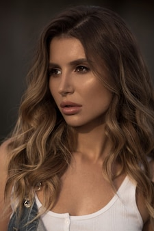 Sexy volwassen vrouw met perfecte make-up en volle lippen in denim overall poseren buitenshuis
