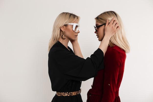 Sexy vriendinnen in stijlvolle jurken met trendy bril kijken elkaar aan en strijken hun haar binnenshuis